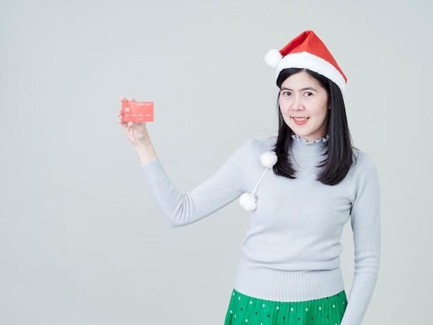 Mulher com chapéu de papai noel na mão mostrando compras com cartões de crédito
