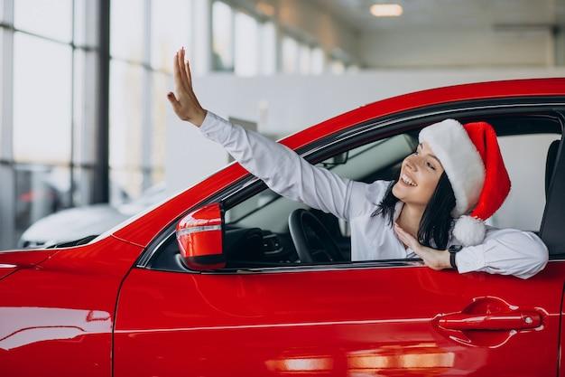 Mulher com chapéu de papai noel perto do carro vermelho em um showroom de carros