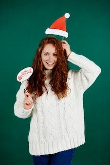 Mulher com chapéu de papai noel segurando banner de natal