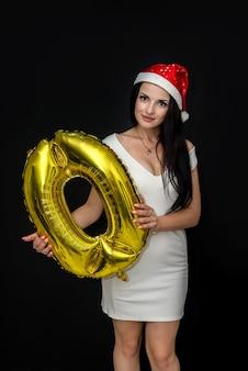 Mulher com chapéu de papai noel segurando um balão de ar 'zero'