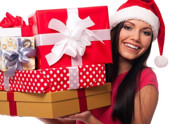 Mulher com chapéu de papai noel segurando uma pilha de presentes de natal
