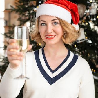 Mulher com chapéu de papai noel segurando uma taça de champanhe
