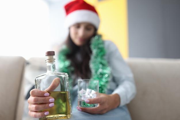 Mulher com chapéu de papai noel vermelho segurando um copo de gelo e uma garrafa de uísque