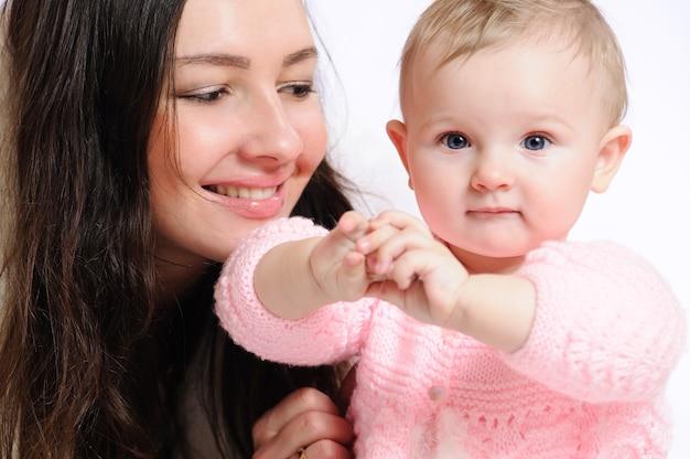 Mulher com chapéu de pele branca e casaco de pele com criança sorrindo e posando enquanto olha para a câmera