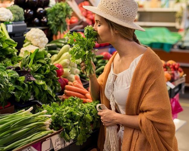 Mulher com chapéu de sol cheirando folhas