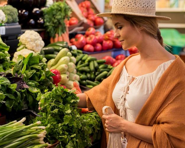 Mulher com chapéu de sol no mercado, vista lateral