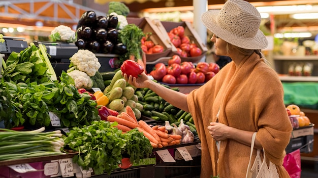 Mulher com chapéu de verão comprando pimentão