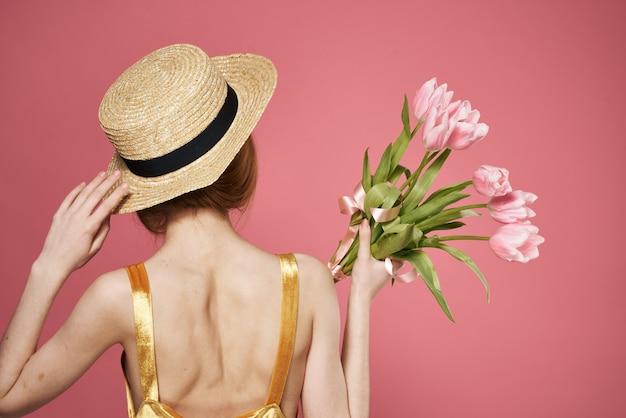 Mulher com chapéu de volta ver o buquê de flores como um fundo rosa de presente