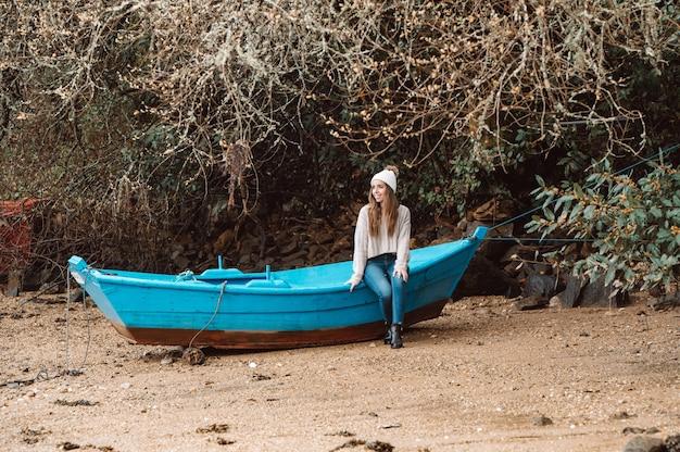 Mulher com chapéu e blusa sentada em um velho barco de madeira atracado na costa arenosa no outono e olhando para longe