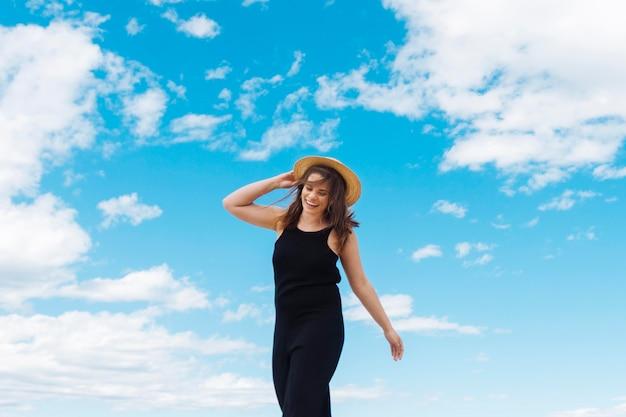 Mulher com chapéu e céu com nuvens