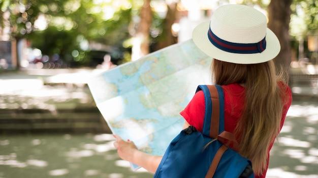 Mulher com chapéu e mapa do lado de fora