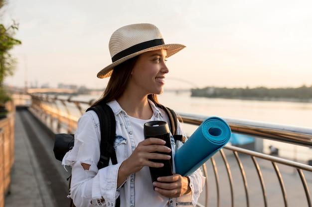 Mulher com chapéu e mochila segurando uma garrafa térmica enquanto viaja