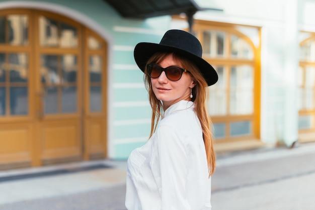 Mulher com chapéu e óculos escuros andando pela cidade no verão