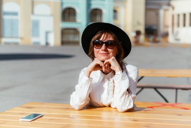 Mulher com chapéu e óculos escuros sorrindo enquanto está sentada em um café no verão