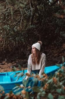 Mulher com chapéu e suéter sentada em um velho barco de madeira atracado na costa arenosa no outono
