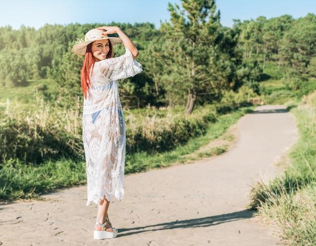 Mulher com chapéu e vestido branco andando