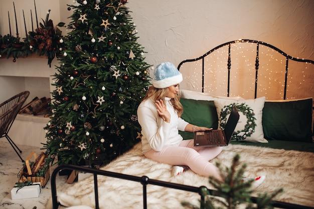 Mulher com chapéu festivo acenando via laptop.