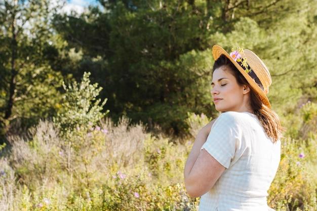 Mulher com chapéu posando com vegetação ao ar livre