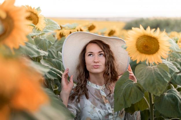Mulher com chapéu posando em campo