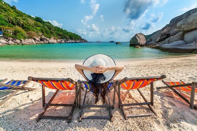 Mulher com chapéu sentado na praia de cadeiras na bela praia tropical. mulher relaxando em uma praia tropical na ilha de koh nangyuan