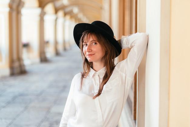 Mulher com chapéu sorrindo e encostada no prédio