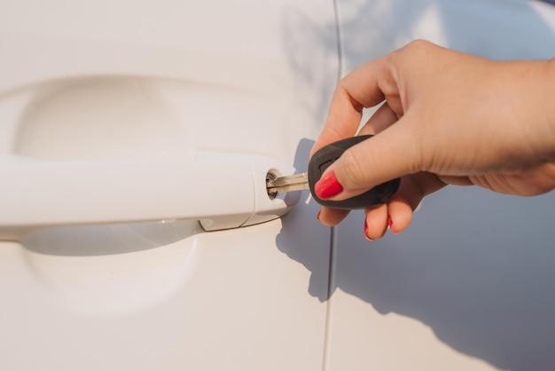 Mulher com chave do carro. abrindo a porta do carro. a mão de uma mulher destranca uma porta de um carro. luz solar. transporte.