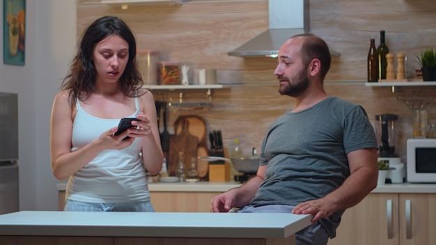 Mulher com ciúme verificando o telefone do homem. mulher suspeita com problemas de confiança, traída, zangada, frustrada e irritada, roubando o smartphone do marido para verificação de fidelidade.