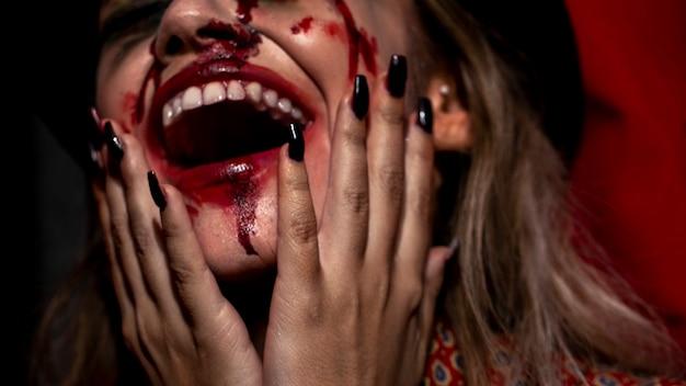 Mulher com close-up de maquiagem de palhaço de halloween