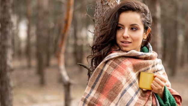 Mulher com cobertor e xícara de chá na natureza