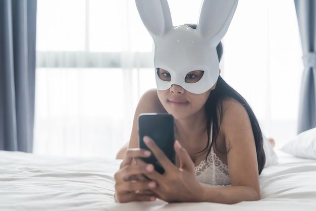 Mulher, com, coelho, máscara, jogo, smartphone