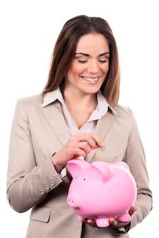 Mulher com cofrinho e moeda