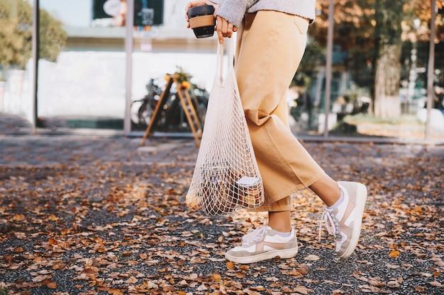 Mulher com compra em saco de rede reutilizável de algodão no fundo da vitrine da loja de resíduos zero