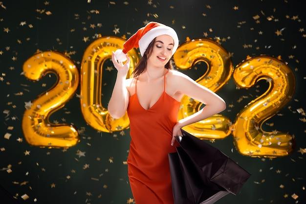 Mulher com compras de chapéu de papai noel, ano novo, compras, vendas de balões de ar na sexta-feira negra