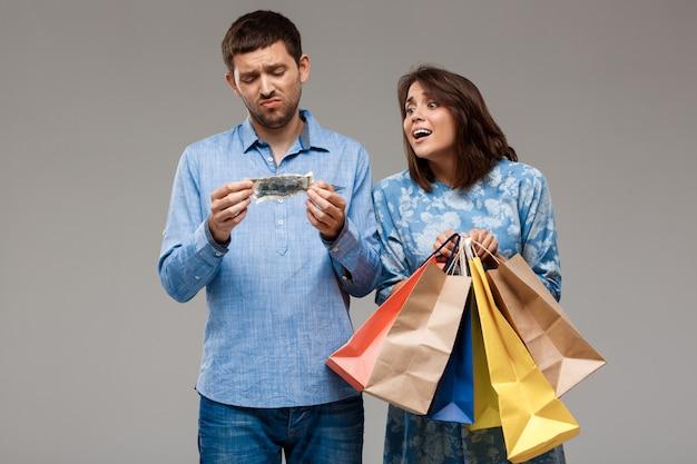 Mulher com compras, homem segurando o último dinheiro sobre parede cinza