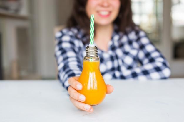 Mulher com conceito de dieta desintoxicante e estilo de vida saudável mostrando suco de laranja