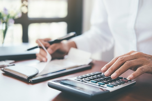 Mulher com contas e calculadora. mulher que usa a calculadora para calcular contas na tabela no escritório.
