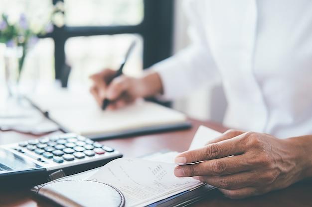 Mulher com contas e calculadora.