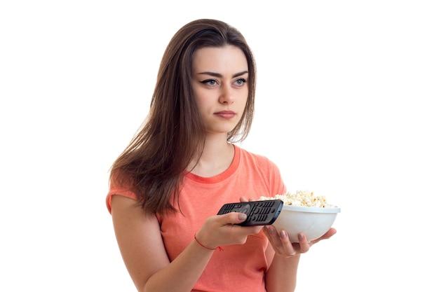 Mulher com controle remoto e pipoca assistindo a uma tv isolada no fundo branco