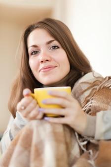 Mulher com copo amarelo em casa
