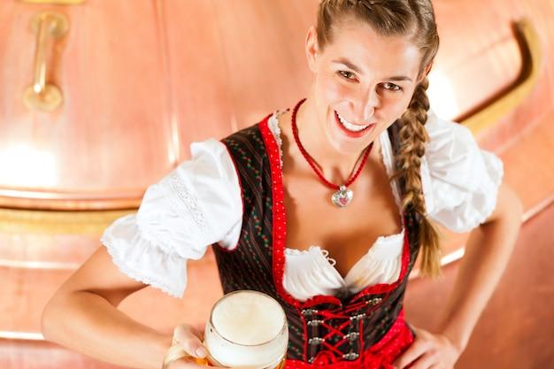 Mulher com copo de cerveja na cervejaria