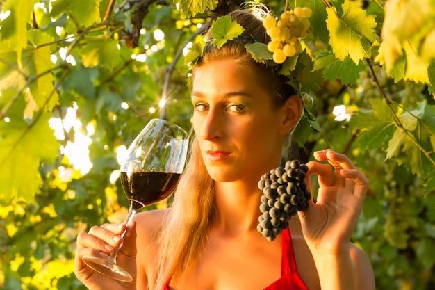 Mulher com copo de vinho em vinhedo