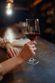 Mulher com copo de vinho tinto, sentado no balcão do bar. uma pessoa feminina em um bar, emoções humanas, atividades de lazer, vida noturna