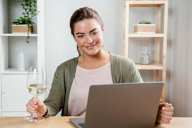 Mulher com copo de vinho usando laptop