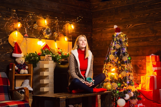 Mulher com copo og bebida quente nas mãos, esperando o ano novo. linda jovem feliz junto à lareira perto da árvore de natal.