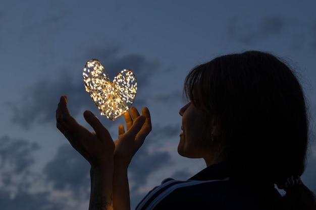 Mulher com coração luminoso altíssimo acima das mãos contra o céu noturno