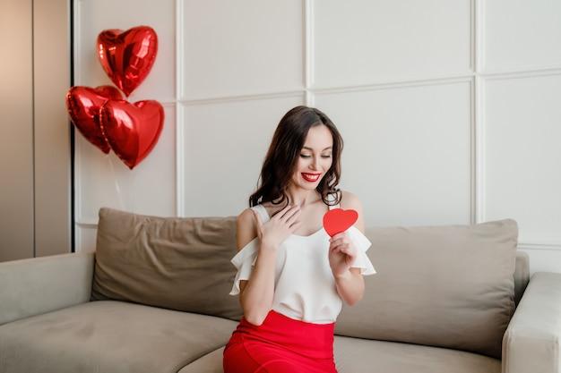 Mulher com coração vermelho em forma de cartão de dia dos namorados, sentada no sofá com balões em casa
