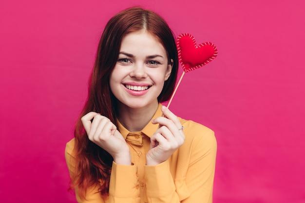 Mulher com coração vermelho feito de tecido em um palito e fundo rosa dia dos namorados