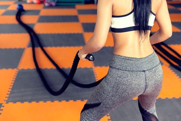 Mulher com corda de batalha em fitness treinamento funcional, tendo perda de peso