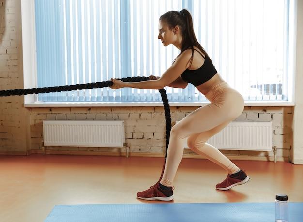 Mulher com cordas de batalha se exercitando na academia