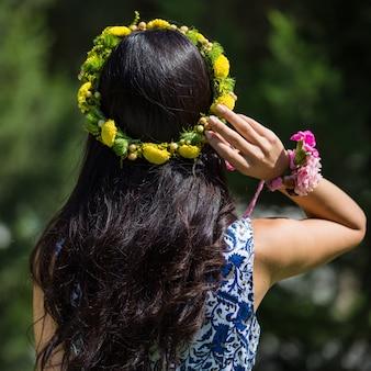 Mulher com coroa de flores amarelas na cabeça.